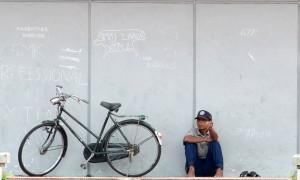 Seorang warga duduk disamping sepeda ontelnya untuk melepaskan penatnya, di Tugu Perjuangan, Simpang Haru Padang, Sumbar,